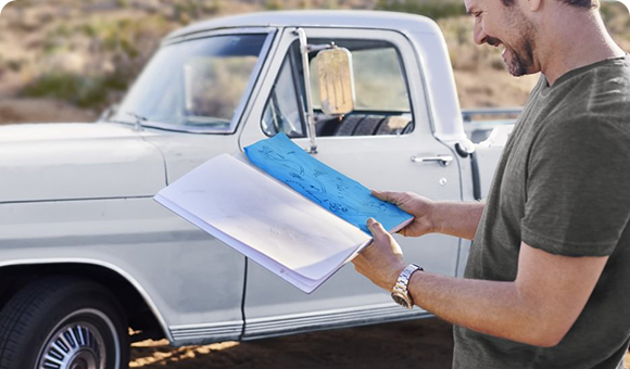 Person reviewing SKYRIZI brochure in front of a pickup truck